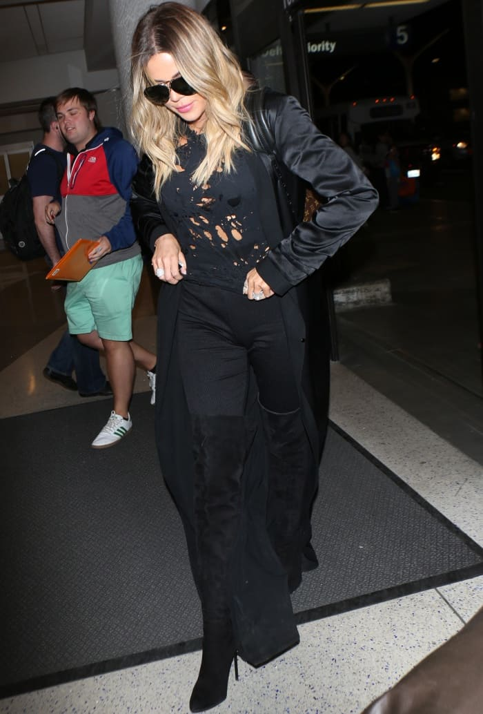 Khloe Kardashian wearing an all-black ensemble with Gianvito Rossi suede over-the-knee boots at LAX