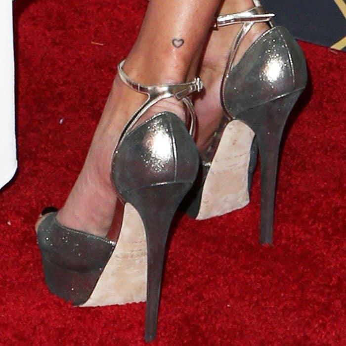 "The model wears the footwear favorite Jimmy Choo ""Pearl"" platform sandals"