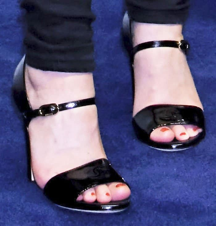 Lily Rose wears a pair of patent mary jane sandals with the Chanel logo embossed on it