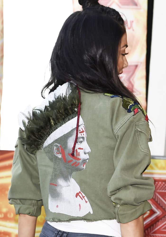 Nicole wears a jacket with a feathered graphic print at the back