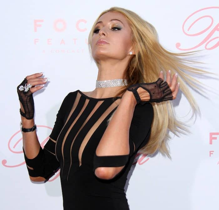 Paris Hilton accessorized with black mesh gloves, a studded choker, and a large cocktail ring