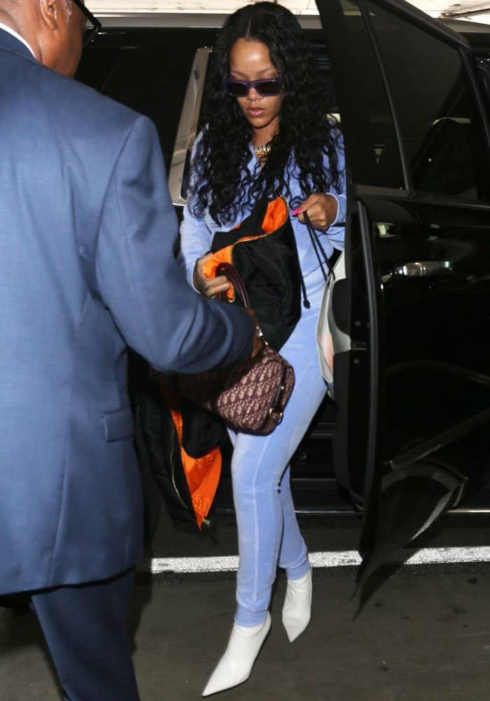 Rihanna steps down from her car before making her way through airport security