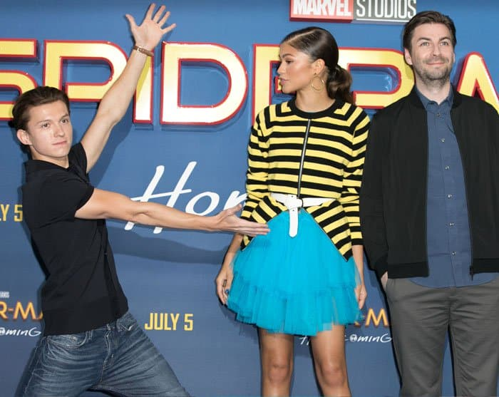 Tom goofs around on the carpet as Zendaya and director Jon Watts pose for the cameras