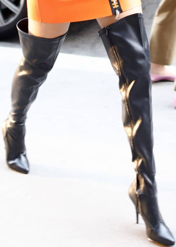Bella Hadid wearing an orange Sami Miro jean jacket, a black bralette, an orange Heron Preston mini skirt and black patent leather thigh-high boots in Paris