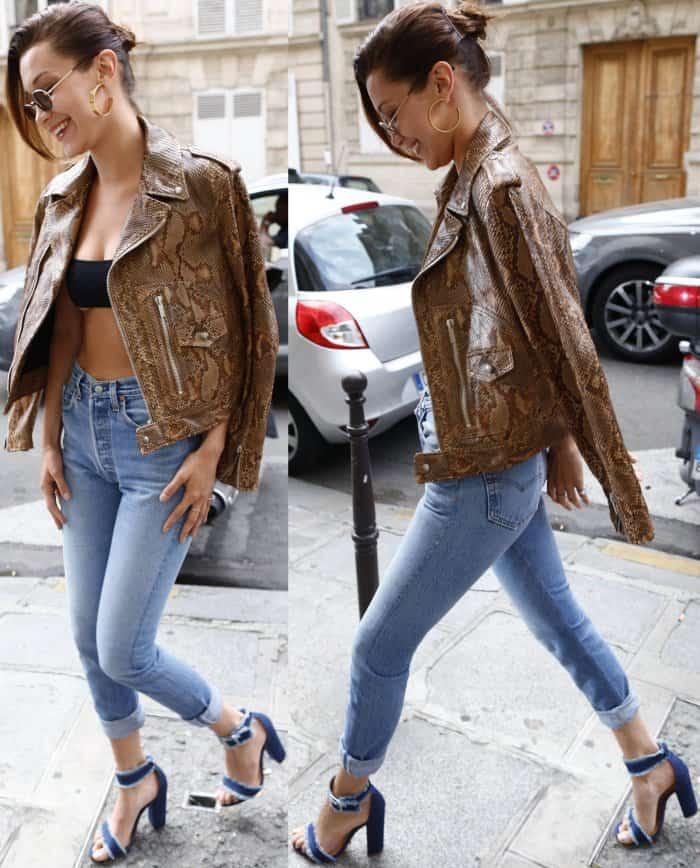 "Bella Hadid wearing a snakeskin motorcycle jacket, black Dior bandeau top, Re/Done jeans, and Schutz ""Janessa"" denim sandals in Paris"