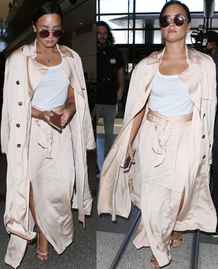 """Demi Lovato wearing an ATM tank top, Elizabeth and James coat and skirt, and Gianvito Rossi """"Portofino"""" sandals in blush satin at LAX"""