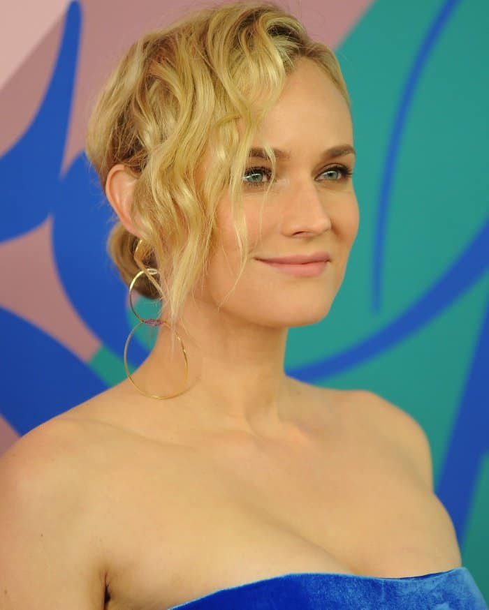 Diane Kruger's side-swept wavy updo, soft pink lips, and mismatched earrings