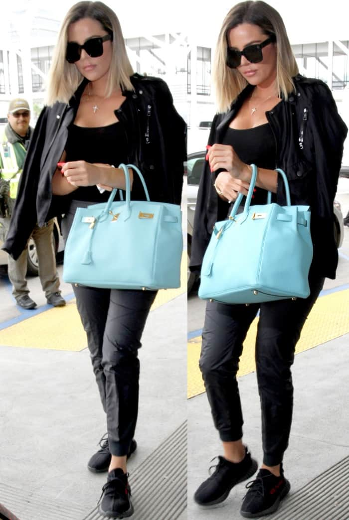 Khloe Kardashian wearing an all-black ensemble with Yeezy x Adidas Boost 350 V2 Sneakers at LAX