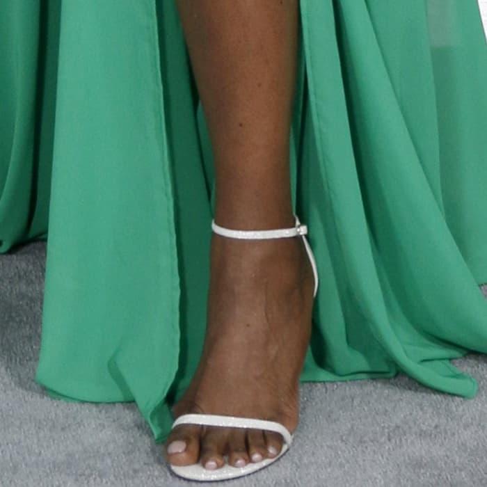 Leslie Jones showing off her feet inwhite Stuart Weitzman ankle-strap heels