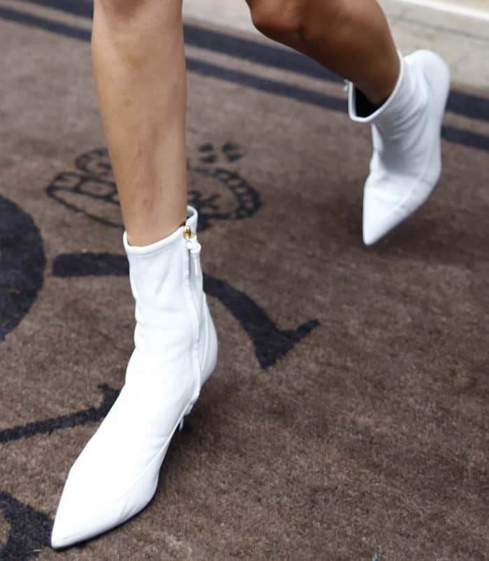 """Bella Hadid in an I.am.gia top and denim skirt and Stuart Weitzman white """"Clingy"""" booties"""