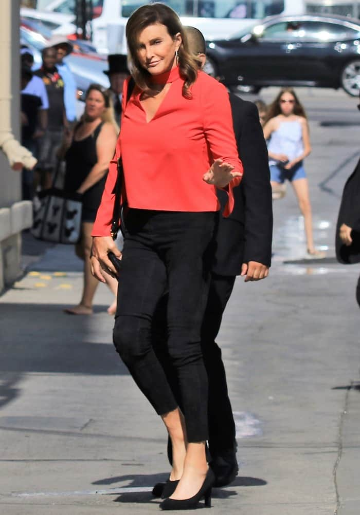 Caitlyn Jenner styled a red long sleeved top with black pants and matching pointy-toe pumps