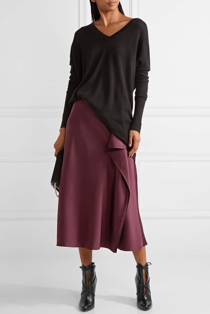Model wearing the 'S.I.T. Rain' boots with The Row's 'Amherst' oversized cashmere and silk-blend sweater and a draped silk-charmeuse midi skirt in a rich grape hue from Cushnie et Ochs