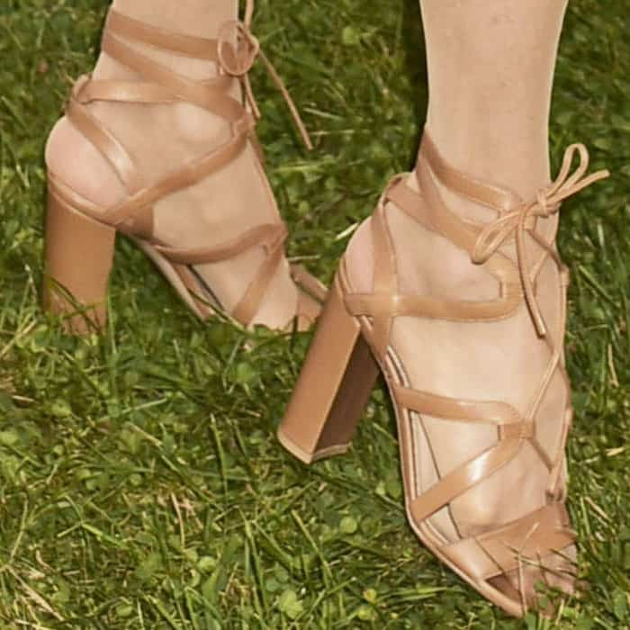 Christie wears a trendy pair of lace-up sandals from Gianvito Rossi