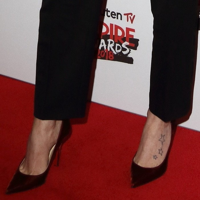 Daisy Ridley's foot tattoos in red velvet'Decoltish' poiny-toe pumps
