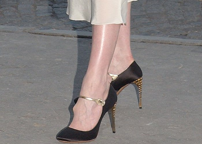 Gwendoline Christie wearing black pumps with gold trims and embellished heels at the Miu Miu Cruise 2018 fashion show during Paris Haute Couture Fashion Week