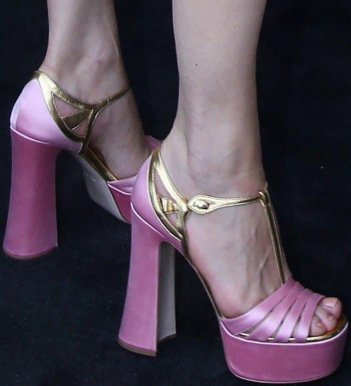 Milla Jovovich wearing pink platform heels at the Miu Miu Cruise 2018 fashion show during Paris Haute Couture Fashion Week