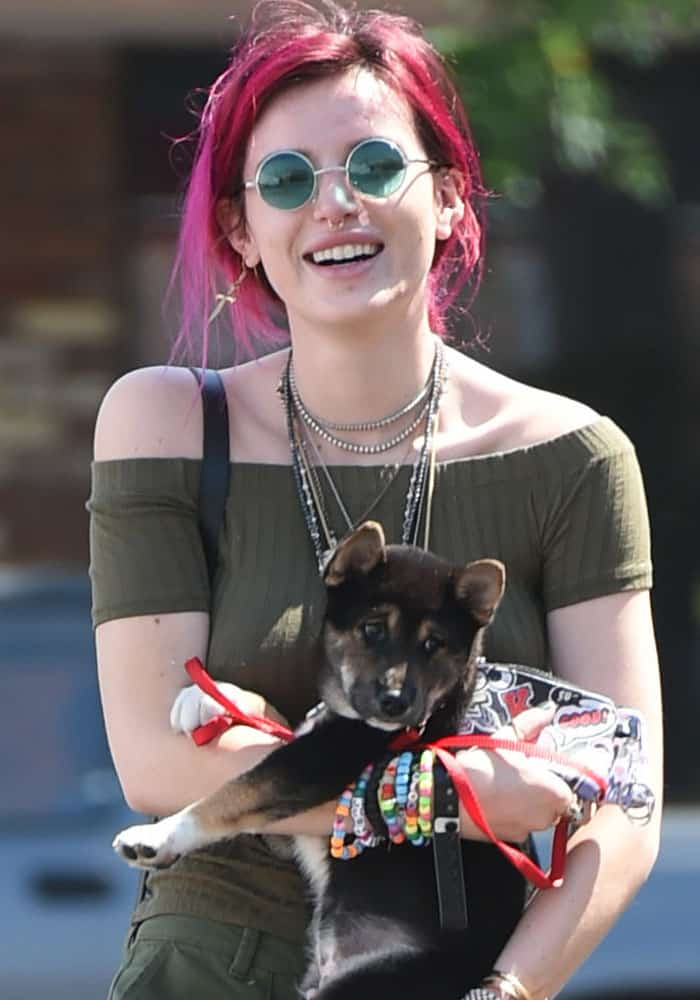Bella Thorne cuddles her puppy as she goes to lunch in Los Angeles on August 6, 2017