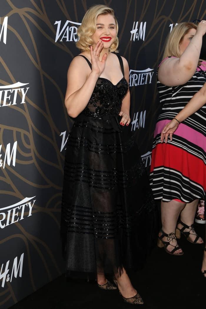 Chloe Moretz in a black embellished Marchesa midi and Jimmy Choo 'Romy' lace pumps