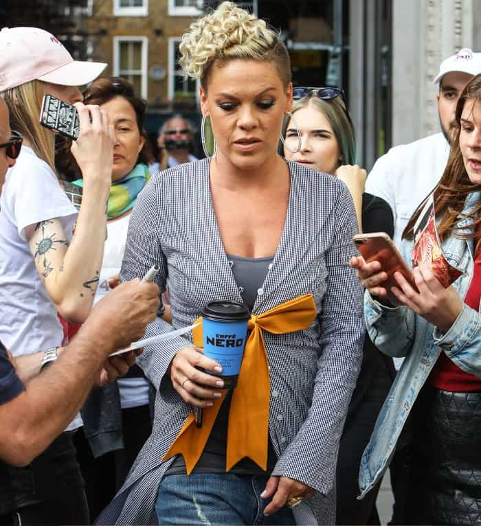 Pink walks through her throng of fans with a cup of coffee in hand
