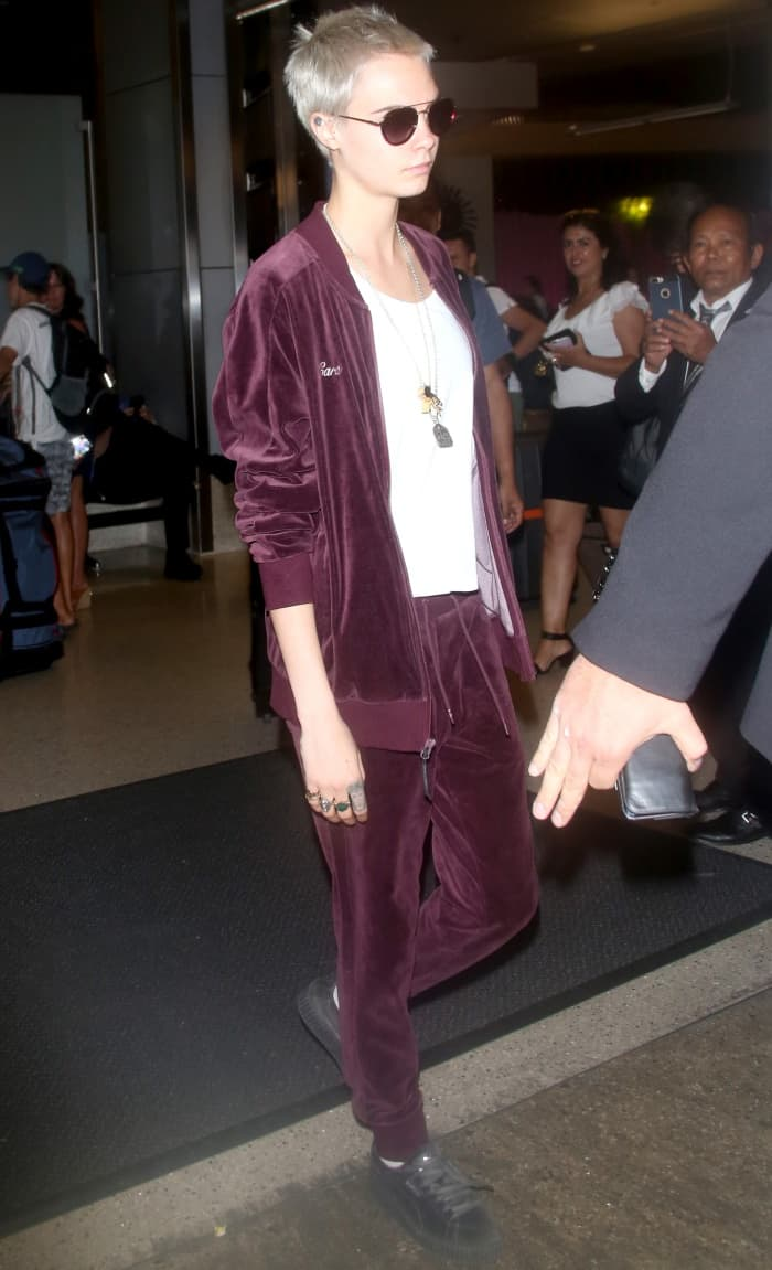 Cara Delevingne wearing a Puma T7 velour tracksuit and Fenty Puma by Rihanna grey velvet lace-up creepers at LAX