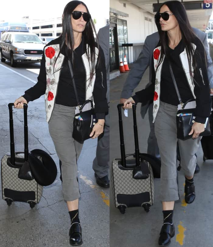 Demi Moore arriving at LAX in a floral-embroidered bomber jacket, grey pants, and black leather slip-on shoes