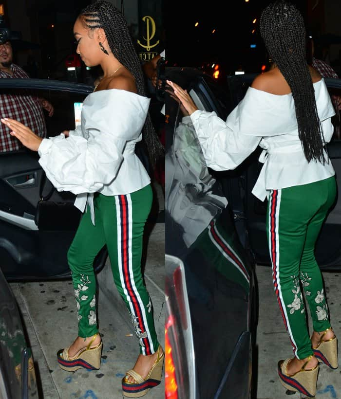 Leigh-Anne Pinnock wearing an off-shoulder wrap shirt, Gucci green jersey stirrup leggings, and Gucci metallic leather platform espadrilles