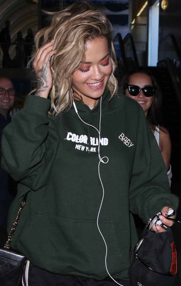 "Rita Ora wearing a dark green hoodie, black trackpants, and white Reebok ""Classic Leather"" sneakers at LAX"