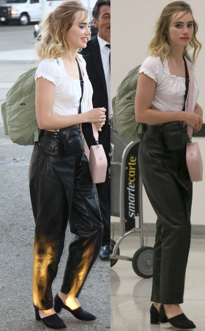 Suki Waterhouse arriving at LAX in a cream-colored crop top, black leather pants, and Mansur Gavriel d'Orsay heels