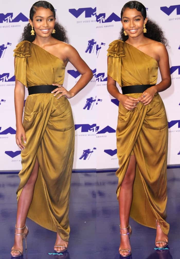 Yara Shahidi in a gold silk gown from Zimmermann featuring a one-shoulder design, a boned bodice, draped detailing, and a crossover skirt with an asymmetrical hem