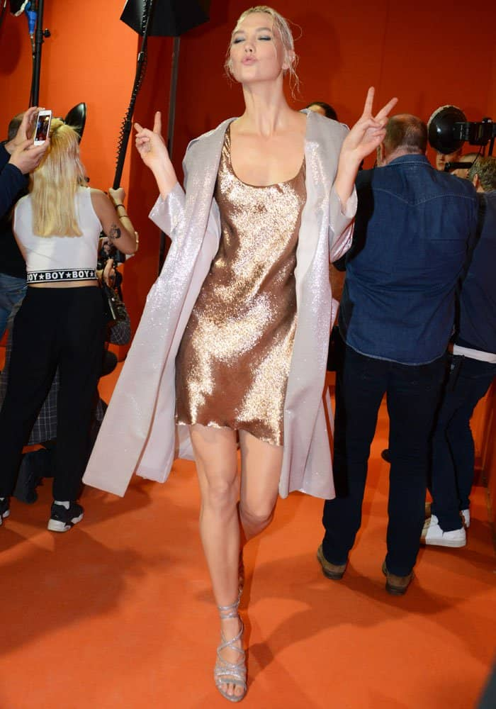 Karlie Kloss flashes the peace sign in a metallic slip dress and long blazer