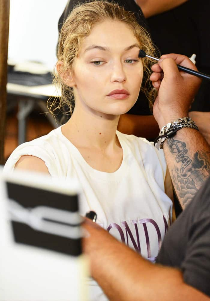 Gigi patiently sits on the makeup chair while artists create the Alberta Ferretti look