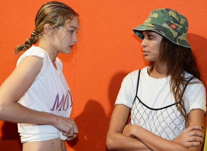 Gigi Hadid and Joan Smalls engage in a serious chat while on standby