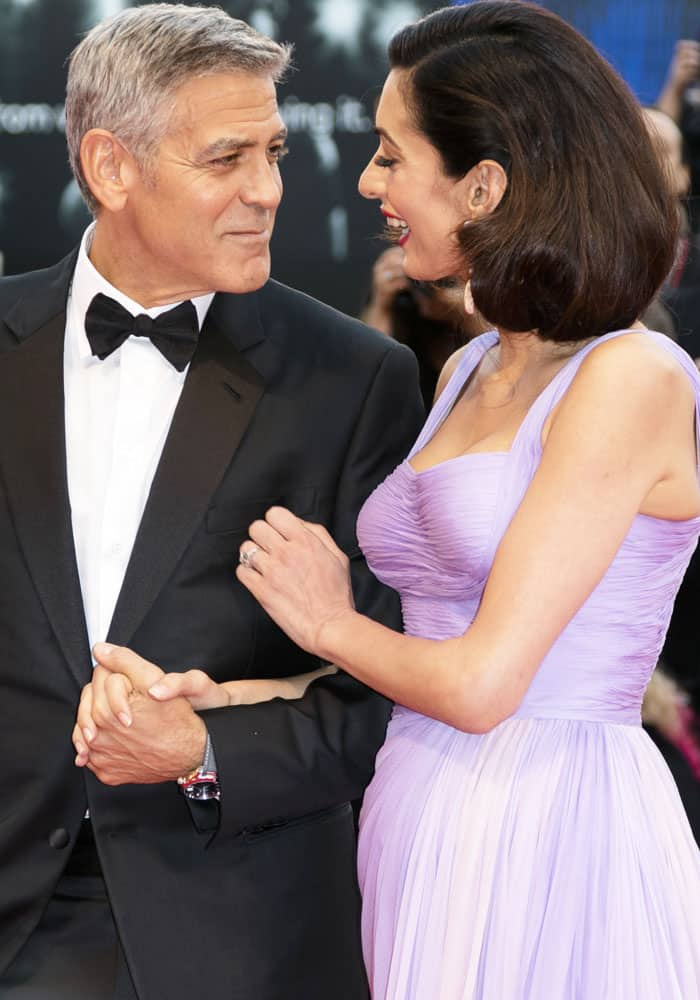 Amal's husband George Clooney gives her a loving stare as the two walked on the red carpet