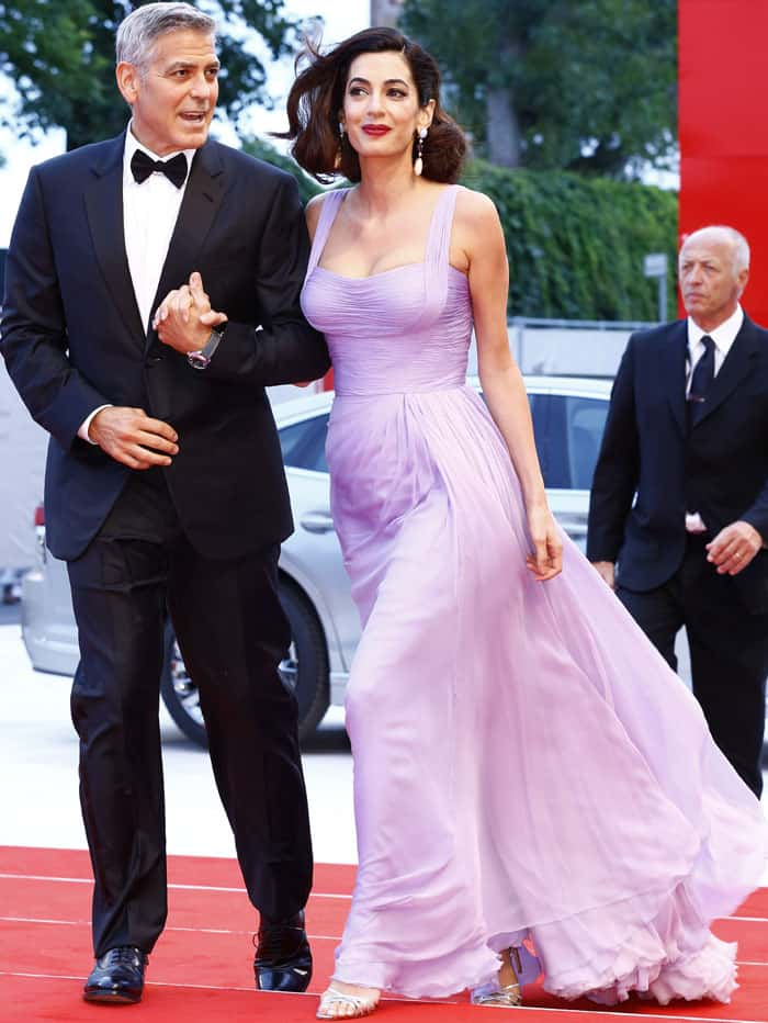 Amal clings on to her husband as she smiles it up for the cameras