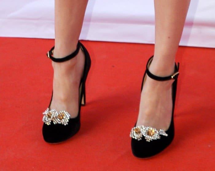 "Emma Roberts wearing a pair of Chloe Gosselin ""Helix"" ankle-strap pumps in black"