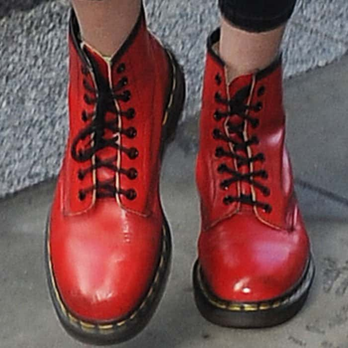 Gigi accentuates her outfit with a pair of bright red Dr. Martens boots
