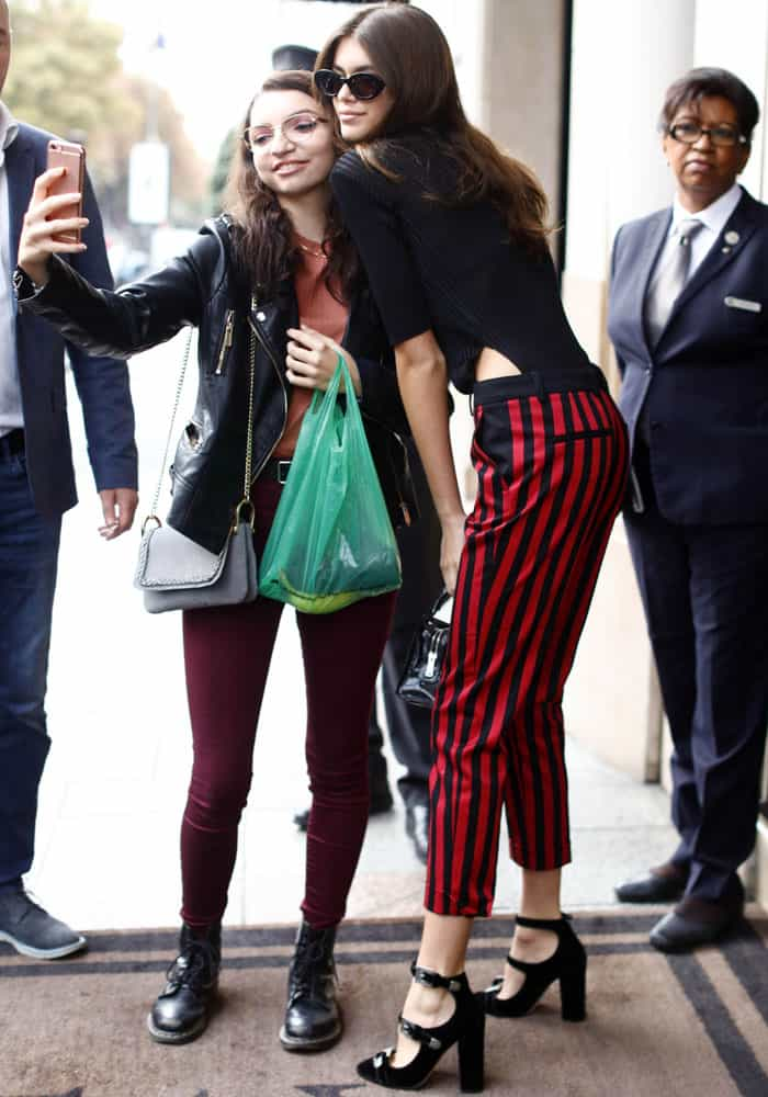 Kaia Gerber stops to pose for photographs with a fan