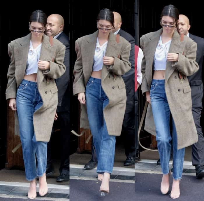 Kendall Jenner out and about NYC in jeans, a white crop top, trench coat and Yeezy Season 2 Lucite sandals.