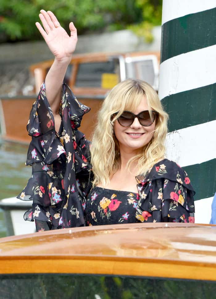 Kirsten waves to the cameras as she arrives at the port
