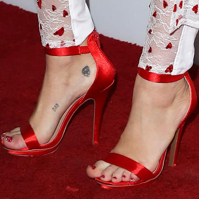 Miley wears a pair of satin ankle strap sandals