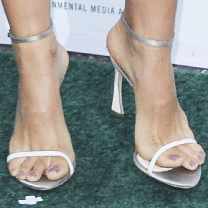 The actress wears a Dior sandal with the signature curved heel