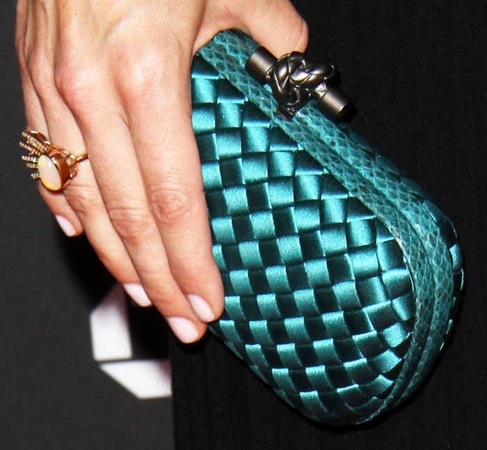 Neve inserts a little personality into her classic look with a woven turquoise clutch