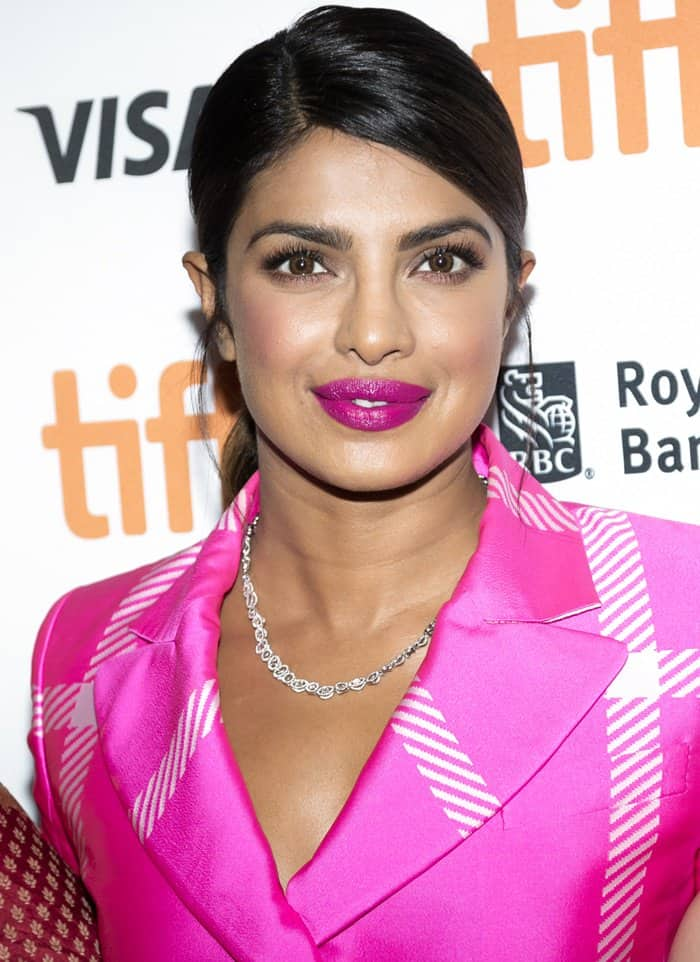 Priyanka Chopra in a pink cropped blazer with matching midi skirt and studded ankle booties.