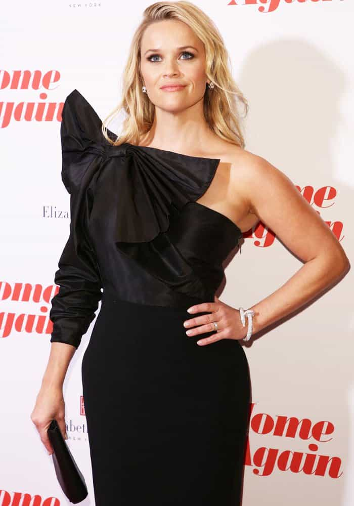 Reese accessorizes her look with Cartier jewelry and a clutch from Valextra