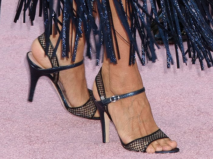 Closeup of Sarah Jessica Parker's SJP Collection slingback sandals with mesh straps and blue glitter heels.