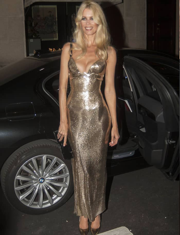 The supermodel still looks impeccable in her gold Versace gown
