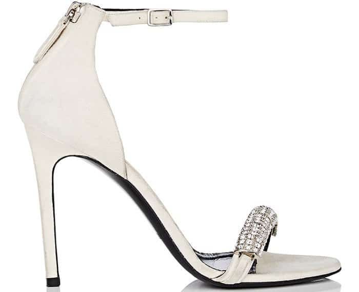 Showcasing a leg-lengthening stiletto heel, this ankle-strap style features a mismatched crystal-embellished strap