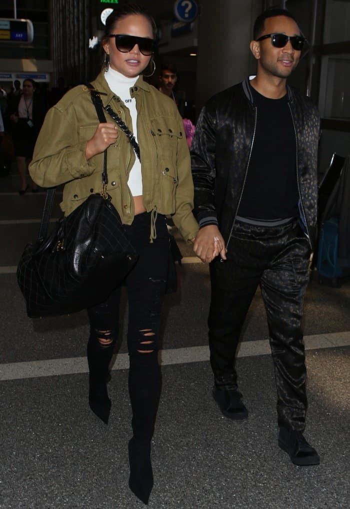 Chrissy Teigen and John Legend walking hand-in-hand at LAX