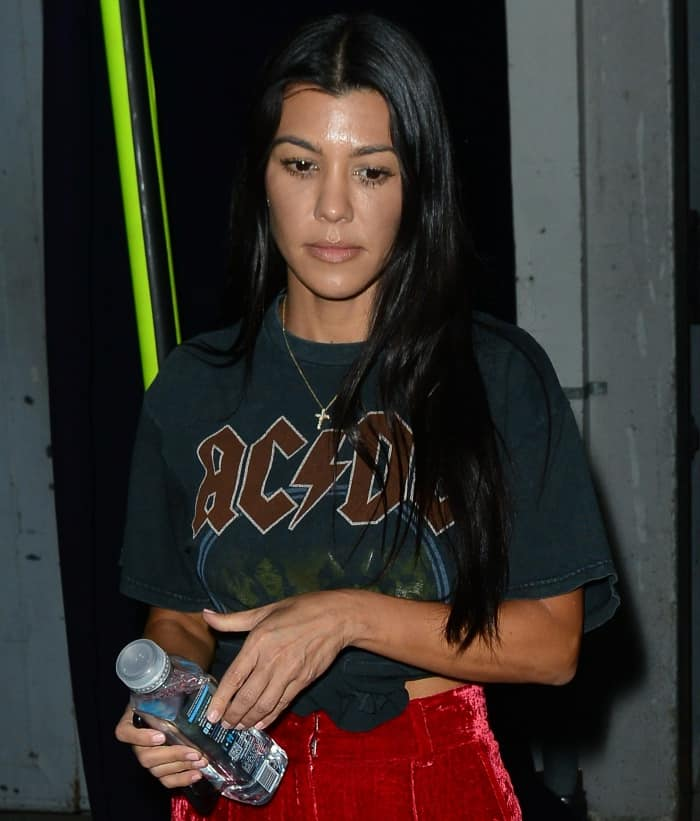 Kourtney Kardashian wearing a vintage AC/DC shirt and AOTC red velvet trousers while leaving a church service in Beverly Hills