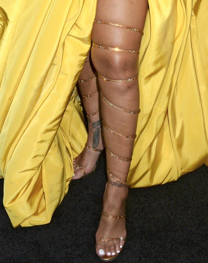 Rihanna wearing custom gold Rene Caovilla over-the-knee gladiator sandals at the Fenty Beauty by Rihanna lunch